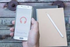 A man hand holding screen shot of google play music . Stock Photo