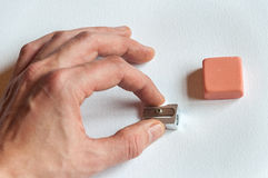 Man hand holding sharpener next to eraser Royalty Free Stock Photography