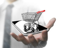 Man hand holding shopping cart with smart phone Royalty Free Stock Photos