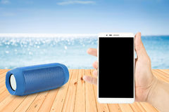 Man Hand holding smart phones and portable speaker on the beach. Hand holding smart phones and portable speaker on the beach Royalty Free Stock Images