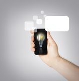 Man hand holding smartphone with light bulb. Environment, ecology and technology - man hand holding smartphone with light bulb sign Stock Image