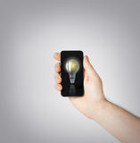 Man hand holding smartphone with light bulb. Environment, ecology and technology - man hand holding smartphone with light bulb sign Royalty Free Stock Photos