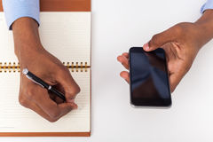 Man hand holding smartphone and writing Stock Images