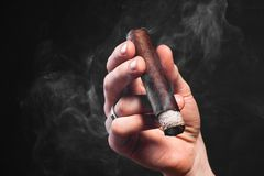 Man hand holding smoking brown cigar Royalty Free Stock Photography