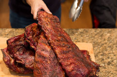 Man hand holding spare ribs on wooden board on family dinner Royalty Free Stock Photos