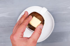 Man hand holding square of white chocolate above cup. Stock Photos