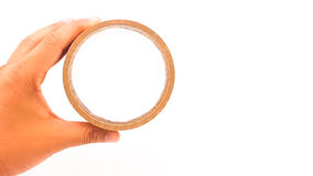 Man hand holding thick brown plastic tape with big core Stock Photo