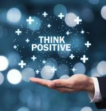 Man hand holding Think Positive words with plus signs. stock images