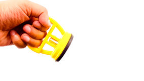 Man hand holding a vacuum sucker in yellow color. Isolated Stock Images