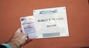 Man hand holding Voter`s car French Carte Polling Station stock photo
