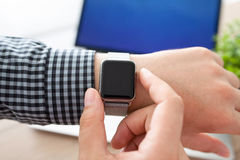 Man hand holding a Watch on the background of laptop stock image