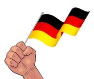 Man hand holding waving Germany flag Royalty Free Stock Image