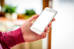 Man hand holding white smartphone in home Stock Photo