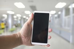 Man hand holding white smartphone in the hospital. Blank screen for display information Stock Image