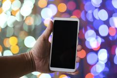 Man hand holding white smartphone in the night. Blank screen for display information Royalty Free Stock Images
