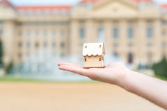 Man hand holding a wooden model house over the blur building Royalty Free Stock Image