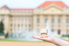 Man hand holding a wooden model house over the blur building Royalty Free Stock Photo