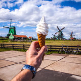 Man hand holds ice cream against background of Dutch wind mills Stock Photos