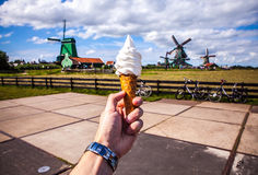 Man hand holds ice cream against background of Dutch wind mills Royalty Free Stock Photos