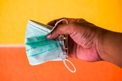 Man hand holds surgical mask with yellow and orange background. General personal protective equipment for use in virus diseases