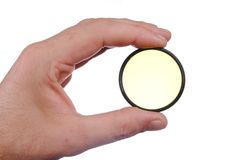Man hand holds a yellow photographic filter. Isolated on white background Stock Photography