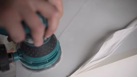 Man hand houdt elektronisch groen poetsmiddel en werkt aan witte oppervlakte stock video