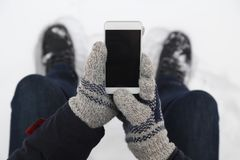 Free Man Hand In Woolen Gloves Holding Blank Screen Smart Phone. Clos Stock Photography - 129650752