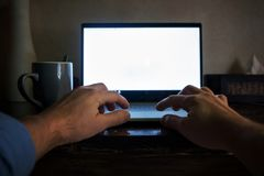 Man hand on laptop keyboard with blank screen monitor on night. View from his position. Royalty Free Stock Photos