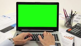 Man hand on laptop keyboard with green screen. Monitor in the office