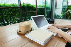 Man hand on laptop on wood table Stock Images
