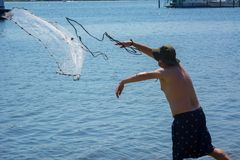 Man that Hand Launches the Fishnet at Sea. On Blur Background royalty free stock image