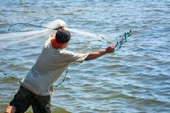 Man that Hand Launches the Fishnet at Sea. On Blur Background royalty free stock photo