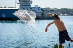 Man that Hand Launches the Fishnet at Sea. On Blur Background royalty free stock photos