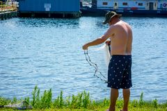 Man that Hand Launches the Fishnet at Sea. On Blur Background stock photography