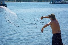 Man that Hand Launches the Fishnet at Sea. On Blur Background royalty free stock photography