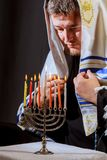 Man hand lighting candles in menorah on table served for hanukka. Man lights candles stock image