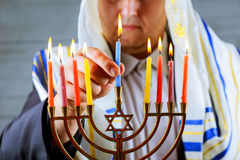 Man hand lighting candles in menorah table served for Hanukkah Royalty Free Stock Photography