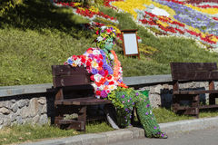 Man in hand made costume from flowers in park. Kyiv, Ukraine-September 5, 2014: street actor dressed in hand made costume from flowers with paint on the face in stock photo