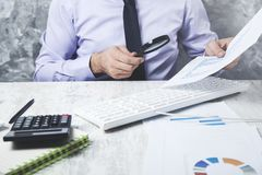 Man hand magnifier with document royalty free stock photo