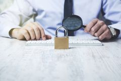 Man hand magnifier and lock. Business man hand magnifier and lock with keyboard stock image