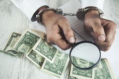 Man hand magnifier and money. Man hand handcuffs with magnifier and money on table stock photo