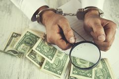 Man hand magnifier and money. Man hand handcuffs with magnifier and money on table stock photos