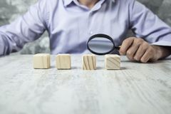 Man hand magnifier with wooden cubes royalty free stock image