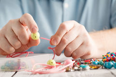 Man hand making earrings of polymer clay. Hobby, handicraft back Royalty Free Stock Image
