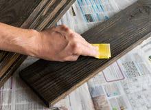 Man hand met de raad van schuurpapierpoetsmiddelen royalty-vrije stock foto's