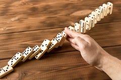 Man hand met domino Het spelen domino's op een houten lijst Rode stukken die, ge?soleerda op witte achtergrond neer vallen royalty-vrije stock afbeeldingen