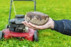Man hand met steen vóór grasmaaimachine Royalty-vrije Stock Afbeelding