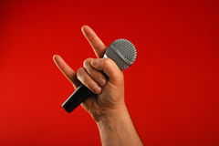 Man hand with microphone and devil horns over red Royalty Free Stock Photo