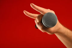 Man hand with microphone and devil horns over red Royalty Free Stock Images