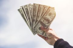Man hand with money on blue sky cloud background.  royalty free stock photos